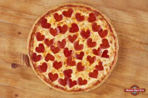heart shaped pepperonis on a pizza