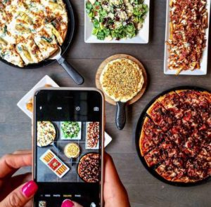 iphone taking picture of pizza dinner spread