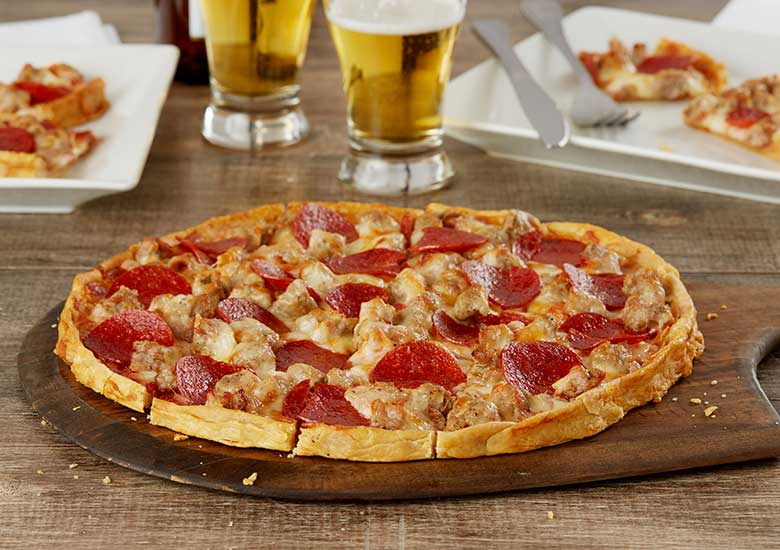 Sausage and Pepperoni Pizza on a pizza paddle sitting on a table in front of a 2 glasses of beer and two plates with square slices of pizza on them