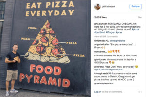 man standing in front of pizza food pyramid mural