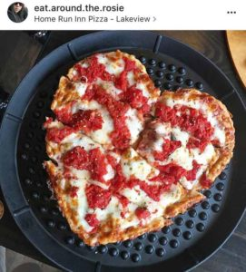 heart shaped pizza topped with plum tomatoes