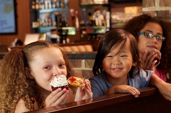 3 kids sitting at a booth in home run inn restaurant enjoying a cupcake, and a slice of pepperoni pizza