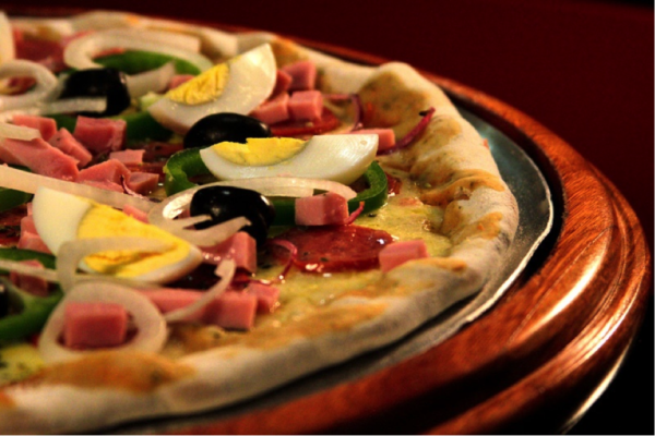 pizza with boiled egg sliced, ham, onions, black olives, and pepperoni