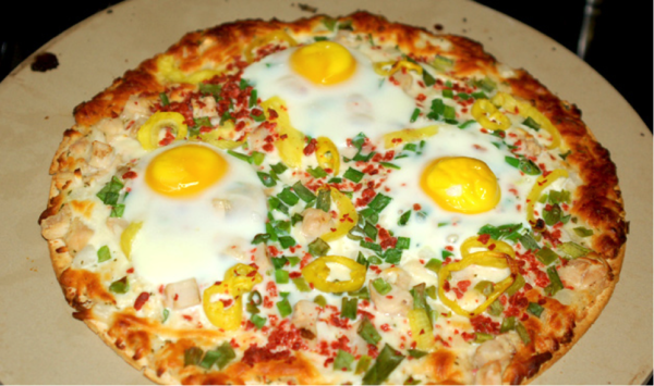 pizza recipe with 3 cracked eggs on top, green onions, and banana peppers