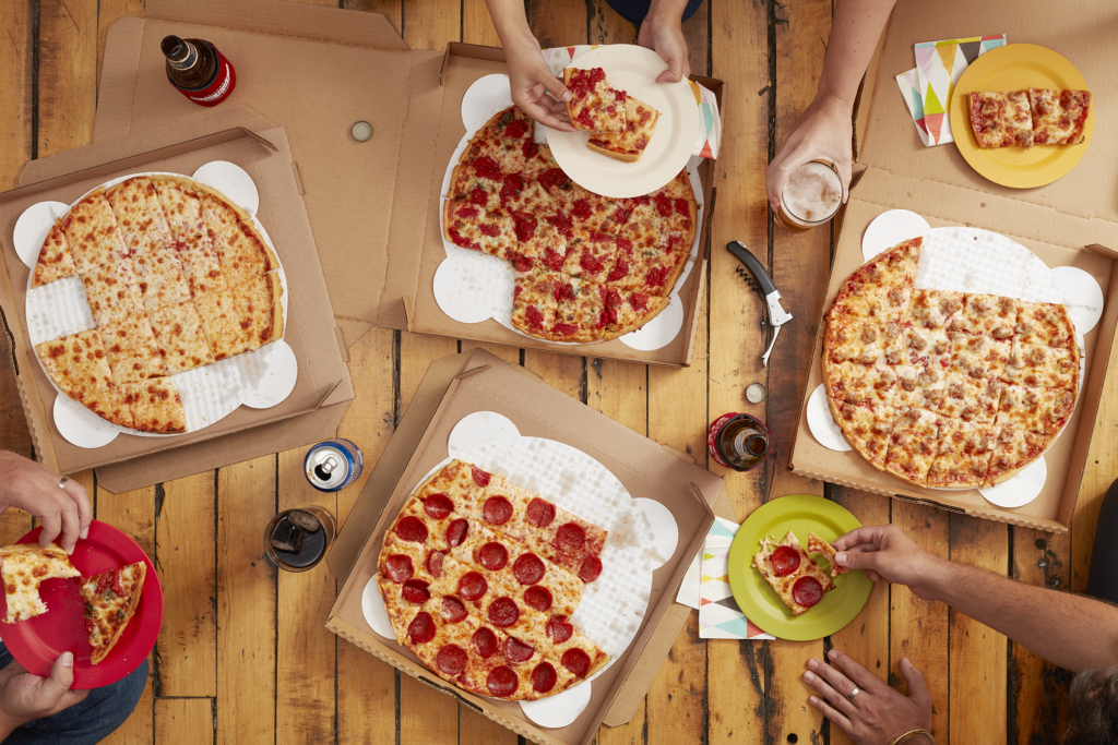 people enjoying multiple pizzas with different toppings
