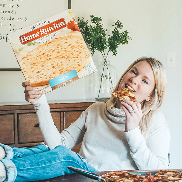 Girl Holding Home Run Inn Pizza box and eating a slice of pizza