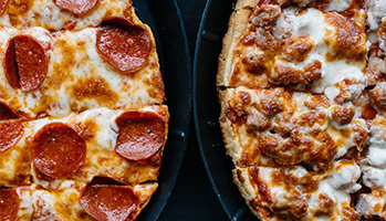 pepperoni pizza next to sausage pizza