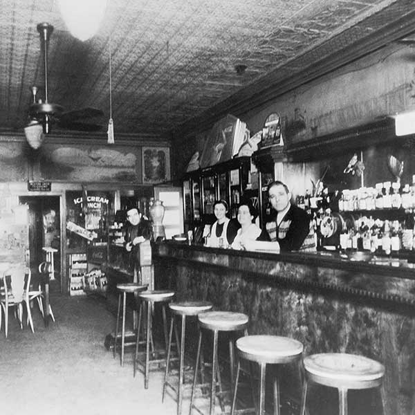 Vintage Black and White photograph of family standing behind the bar at Home Run inn's tavern