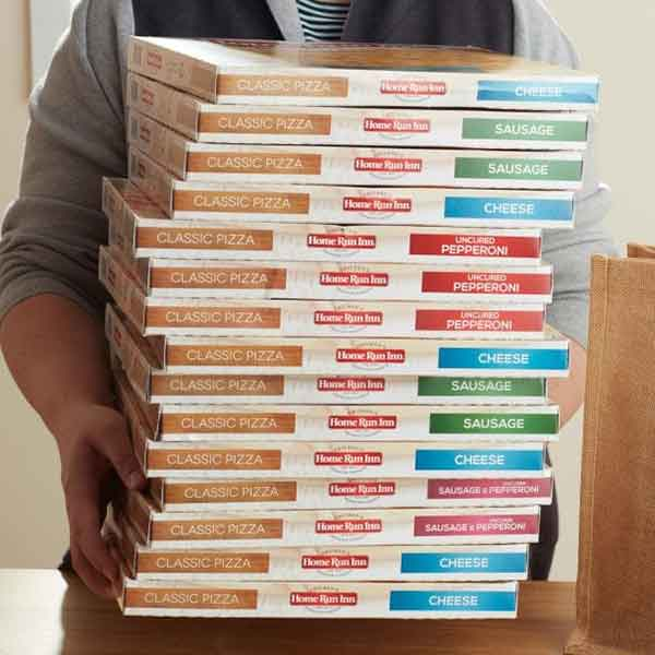 women holding a tall stack of frozen pizza boxes