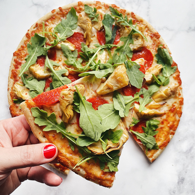 Artichoke, pepperoni and spring mix on a pizza slice